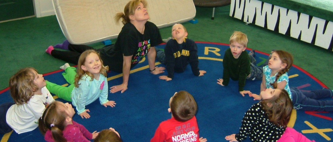 Mrs. Susan and students stretch out before gymnastics